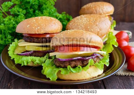 Many hamburgers at home (bun tomato cucumber onion rings lettuce pork chops cheese) in a clay bowl on a wooden background. Close-up