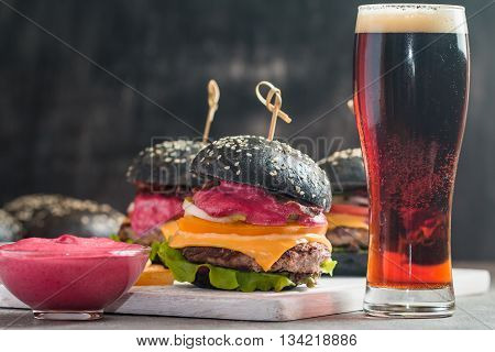 Gourmet black burger with berry sauce and beer on wooden table and dark background