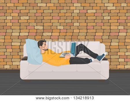 Man lying relaxing on the sofa couch and using laptop