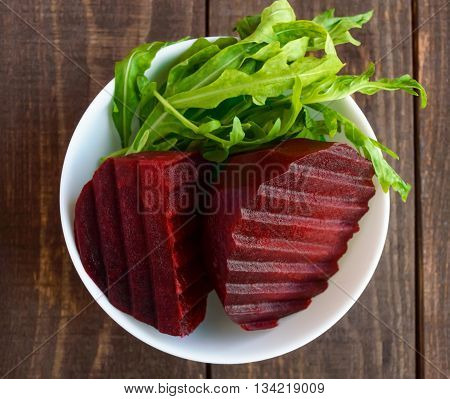 Cooked beets and arugula in a white bowl. For salads. Vegan. top view