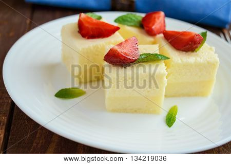 Delicate cottage cheese and creamy souffle in the form of cubes decorating with mint leaves and fresh strawberries on a white plate. Close up