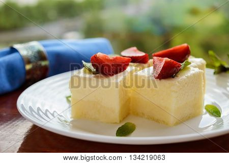 Delicate cottage cheese and creamy souffle in the form of cubes decorating with mint leaves and fresh strawberries