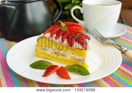 A piece of banana-strawberry sponge cake decorating with mint leaves on a white plate and cup of tea on wooden background