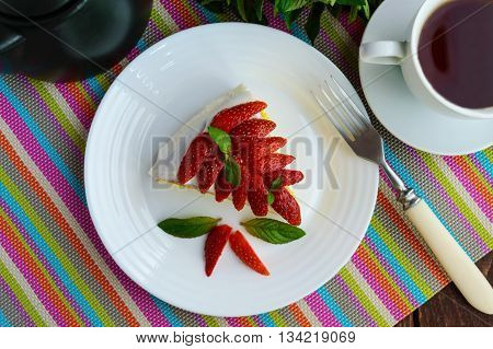 A piece of banana-strawberry sponge cake decorating with mint leaves on a white plate and cup of tea. The top view