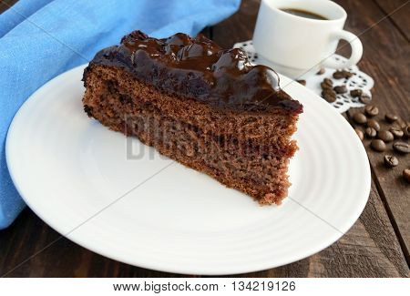 Chocolate and cherry cake. A piece on a white plate close-up. A cup of coffee.