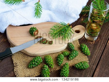 Young green fir cones on the wooden background. Chopping knife cones for making medicinal infusion.