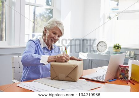 Senior Woman At Home Addressing Package For Mailing