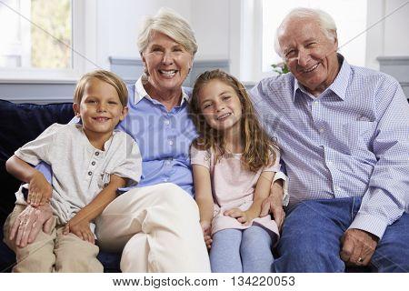 Portrait Of Grandparents And Grandchildren Sitting On Sofa