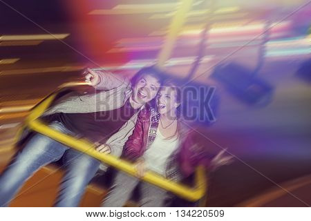Beautiful young couple having fun at an amusement park