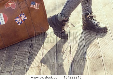 Urban young girl standing on the street next to a suitcase