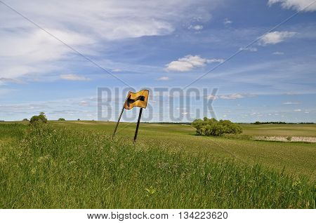 A crumpled  road sign in a grassy field indicates a curve in the road which appears illusive.