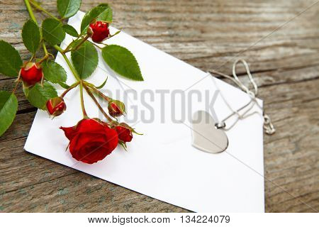 a love letter with heart and rose on an old table