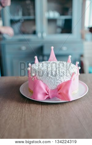 cake in the form of a pink crown with white pearls and candle