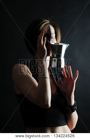 Young barista girl with coffee Moka pot on black background