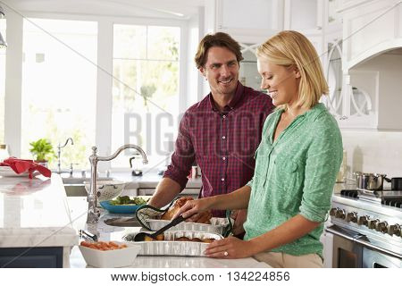 Couple Make Roast Turkey Meal In Kitchen Together