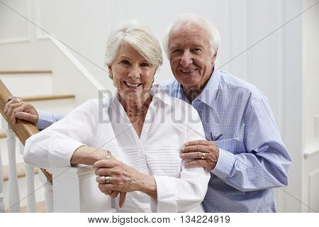 Portrait Of Senior Couple Standing By Staircase At Home
