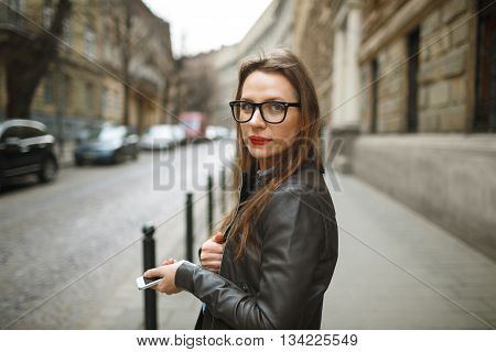 Businesswoman walking down the street while talking on smart phone. Caucasian business woman busy