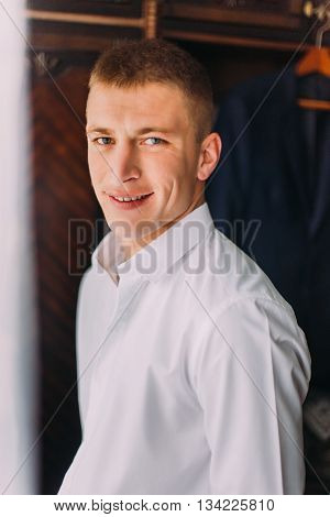 Young happy man. Handsome stylish guy with white shirt looking at camera and smiling while standing in dressing room.