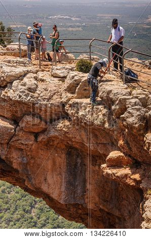 KESHET (ARCH) CAVE, UPPER GALILEE, ISRAEL - MAY 12, 2016: Man prepare himself to rappel down from the top of the rocky arch.