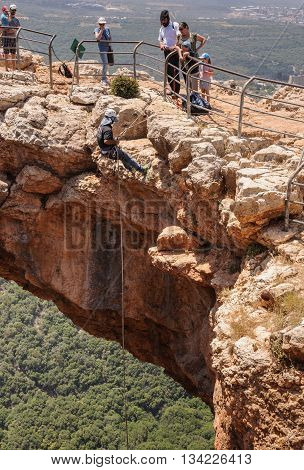 KESHET (ARCH) CAVE, UPPER GALILEE, ISRAEL - MAY 12, 2016: Man rappelling down from the top of the rocky arch of the cave.