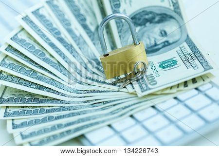 Security lock on dollar bills with white computer keyboard - breach of security online payments concept