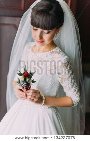 Beautiful bride posing with cute floral boutonniere indoors before her wedding.