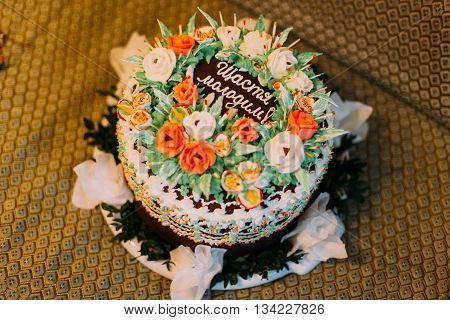 Chocolate cream cake with white and orange roses and holiday inscription.