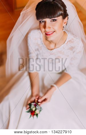 Excited bride in gorgeous white dress waiting for her wedding posing with cute floral boutonniere sitting in dressing room before the ceremony.