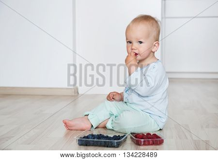 Cute child eats berries sitting on the floor