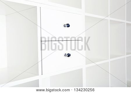 Empty shelves in white wooden rack close up