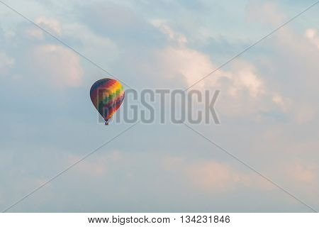 colorful hot air balloon in blue cloudy sky