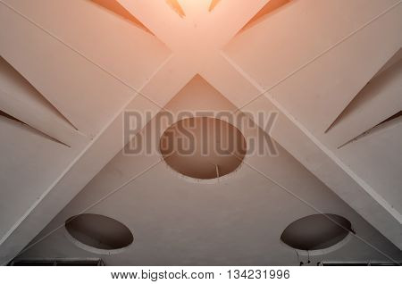 Closeup of architecture elements of stone ceiling. Architecture urban minimalist view of architecture ceiling details with reflected warm light above