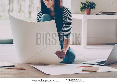 Confident architect. Close-up of confident young beautiful woman examining blueprint while sitting on the floor at home