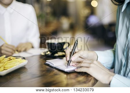 two women writing in their notes in a coffee shop