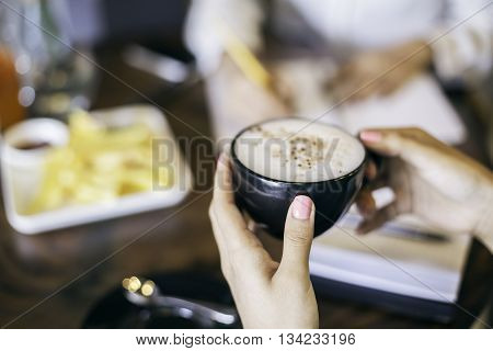 woman holding a black cup of cappuccino
