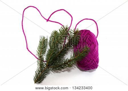 Big heart made of purple skein of thread with pine branch