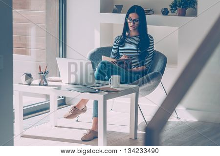 Making some notes. Confident young beautiful woman making notes in notebook while sitting at her working place