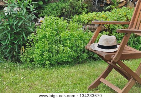 straw hat in a wooden chair in a greenery garden