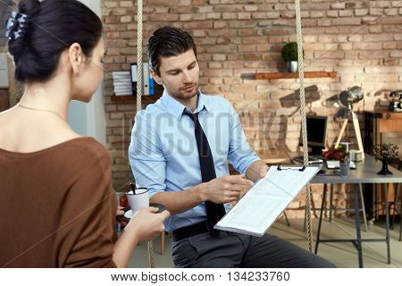 Young businesspeople working in modern office, talking, holding document.