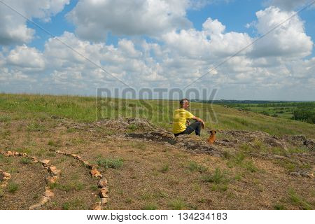 Dreaming man sitting with a dog in the prairie and looking into the distance. Sunny day in a prairie desert. Azov steppes Ukraine.