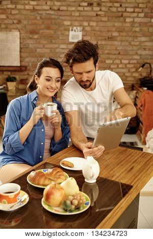 Young couple sitting at morning table, using tablet computer, having breakfast.