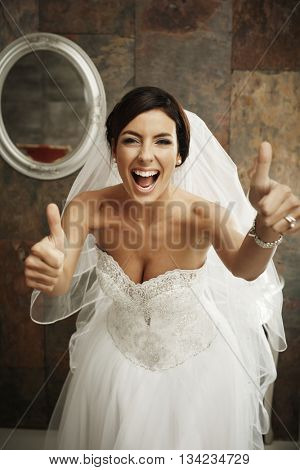 Happy bride in full glamour showing thumbs up.