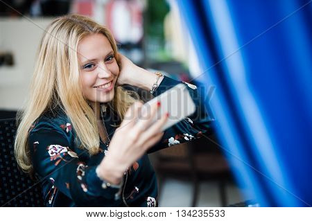 Gorgeous smiling blonde woman making self portrait with mobile phone camera while sitting in modern cafe inside, charming happy female posing while photographing herself for social network picture.