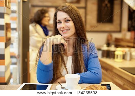Portrait of attractive young woman smiling happy in cafeteria.