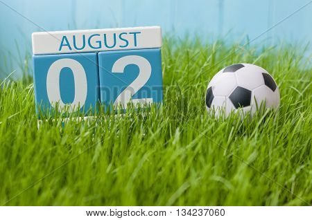August 2nd. Image of august 2 wooden color calendar on green grass lawn background with soccer ball. Summer day. Empty space for text.