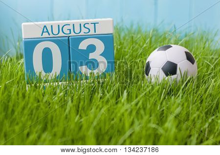 August 3rd. Image of august 3 wooden color calendar on green grass lawn background with soccer ball. Summer day. Empty space for text.