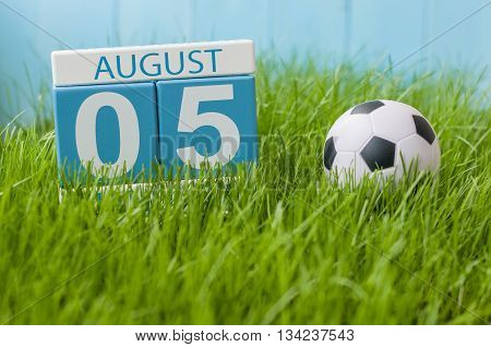 August 5th. Image of august 5 wooden color calendar on green grass lawn background with soccer ball. Summer day. Empty space for text.