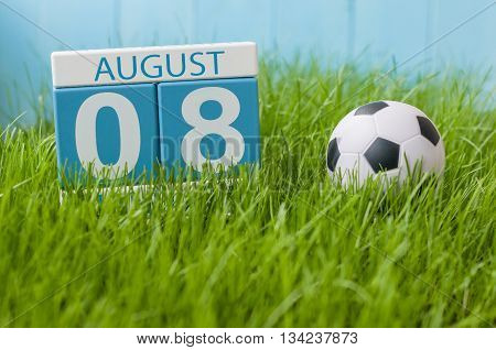 August 8th. Image of august 8 wooden color calendar on green grass lawn background with soccer ball. Summer day. Empty space for text.