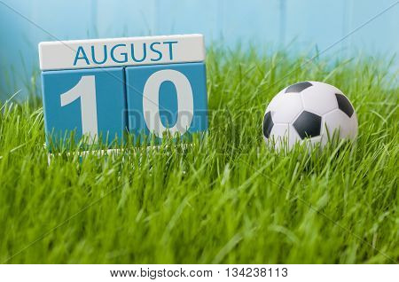 August 10th. Image of august 10 wooden color calendar on green grass lawn background with soccer ball. Summer day. Empty space for text.