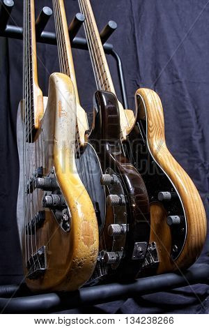 Three electric bass guitar standing on a stand